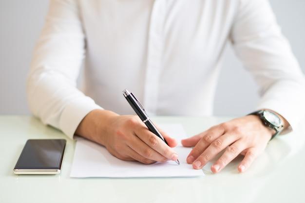 Primo piano dell'uomo che lavora e che scrive sul foglio di carta
