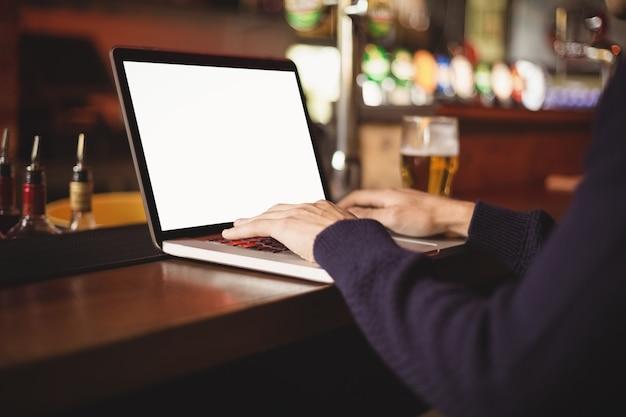 Primo piano dell'uomo che per mezzo del computer portatile