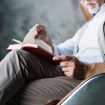 Primo piano dell'uomo che si siede sul libro di lettura della sedia