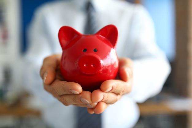 Primo piano dell'uomo che tiene banca piggy rosso brillante. mano di persone con contenitore per risparmiare denaro. contanti per acquisti futuri.