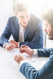 Primo piano dell'uomo d'affari che esamina il suo partner che analizza il rapporto finanziario della società