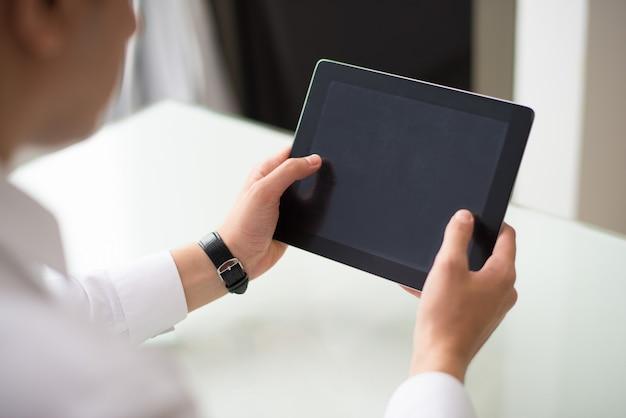 Primo piano dell'uomo d'affari che lavora con la compressa digitale nell'ufficio