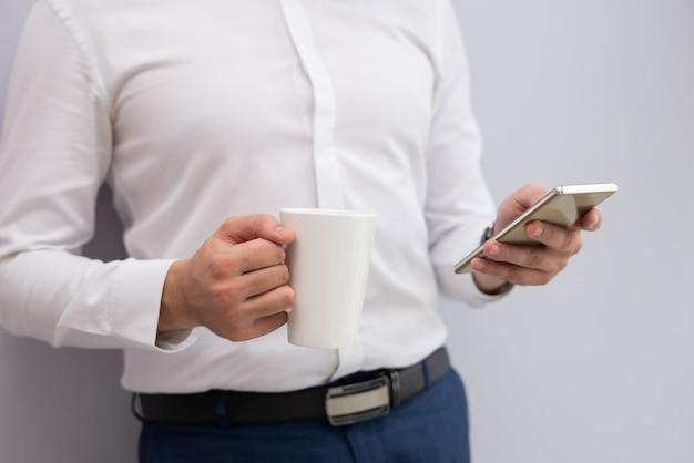 Primo piano dell'uomo d'affari che sta con la tazza di tè facendo uso del telefono cellulare