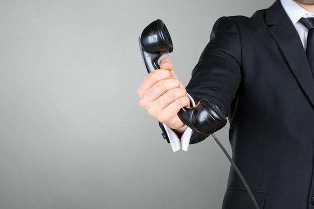 Primo piano dell'uomo d'affari che tiene un ricevitore telefonico