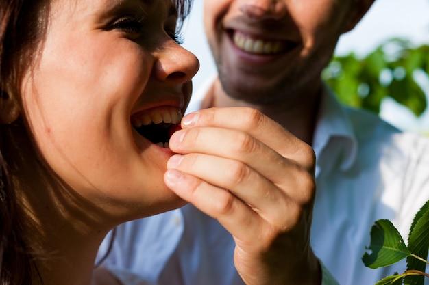 Primo piano dell'uomo felice che alimenta le sue ciliege della donna dall'albero