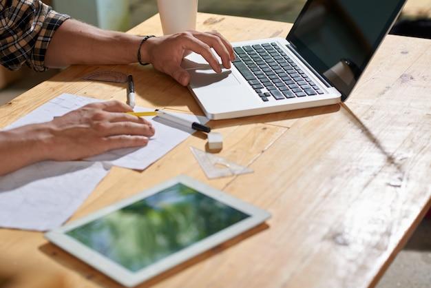 Primo piano dell'uomo potato che schizza un progetto sul foglio di carta e che per mezzo del computer portatile