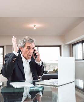 Primo piano dell'uomo senior che esamina computer portatile che parla sul cellulare nell'ufficio