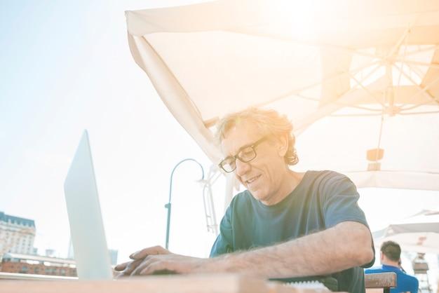 Primo piano dell'uomo senior che scrive sul computer portatile al caffè all'aperto