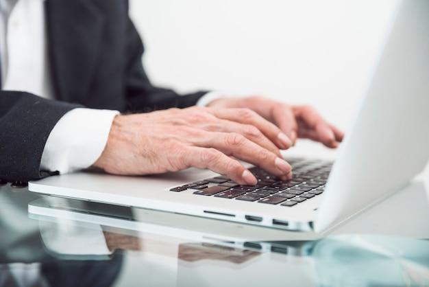 Primo piano dell'uomo senior che scrive sul computer portatile sopra lo scrittorio di vetro