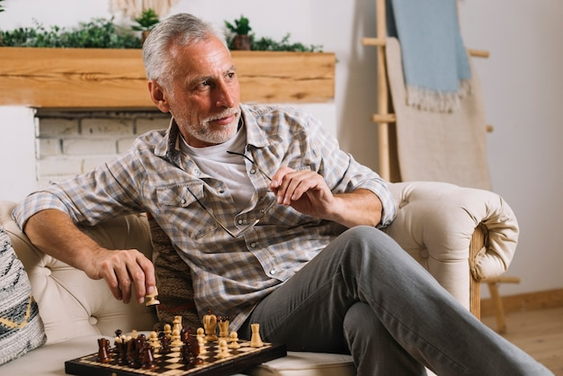 Primo piano dell'uomo senior che si siede sul sofà che gioca scacchi