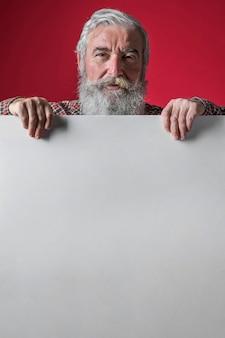Primo piano dell'uomo senior che sta dietro il cartello bianco contro il contesto rosso