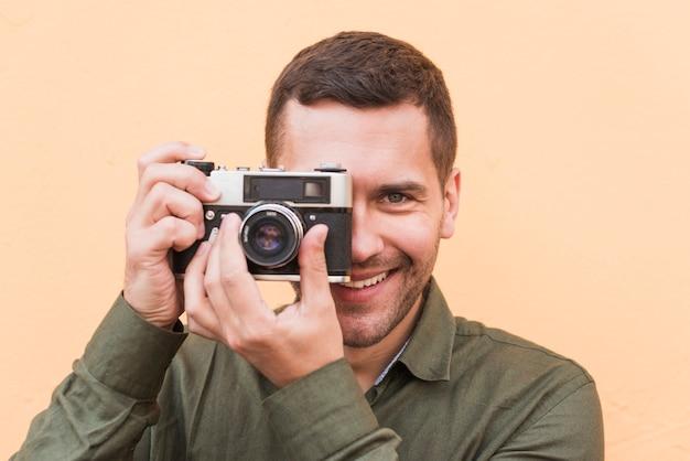 Primo piano dell'uomo sorridente che cattura maschera con la macchina fotografica