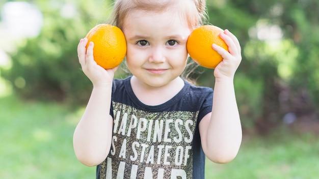 Primo piano della bambina che tiene le arance in mano