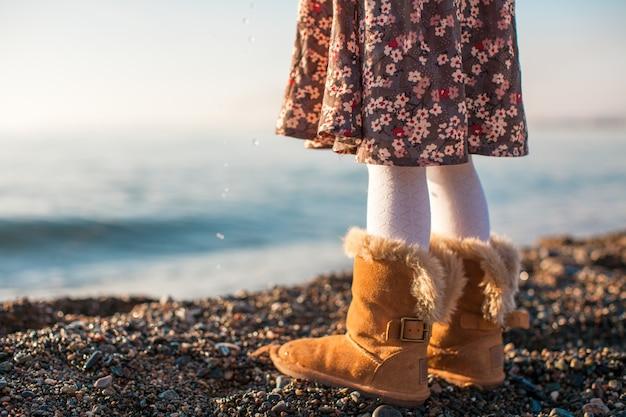 Primo piano della bambina delle gambe nel fondo accogliente degli stivali di pelliccia il mare