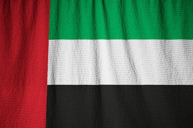 Primo piano della bandiera arruffata degli emirati arabi uniti, bandiera degli emirati arabi uniti che soffia in vento