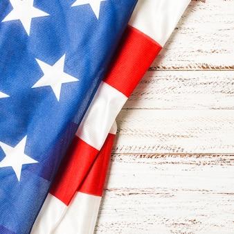 Primo piano della bandiera usa piegata con strisce e stelle su fondo in legno