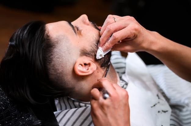 Primo piano della barba del cliente di taglio del barbiere di vista laterale