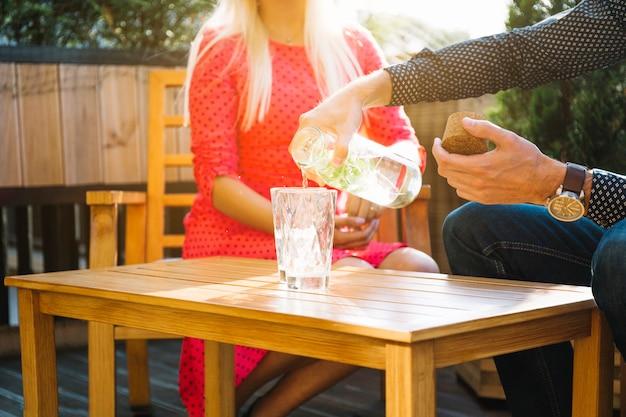 Primo piano della bevanda di versamento della mano dell'uomo in vetri sulla tavola di legno