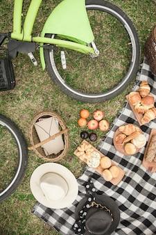 Primo piano della bicicletta; cappelli; cestino da picnic; pane e frutta nel parco