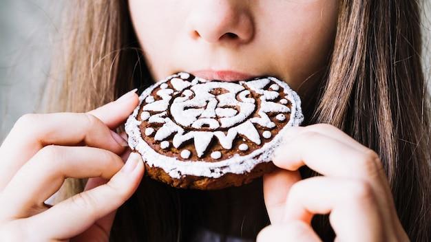 Primo piano della bocca della ragazza che mangia i biscotti di glassa