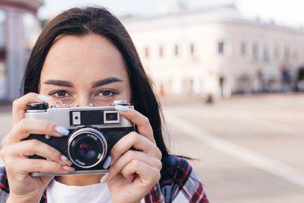 Primo piano della bocca nascondentesi della donna con la tenuta della macchina fotografica retro