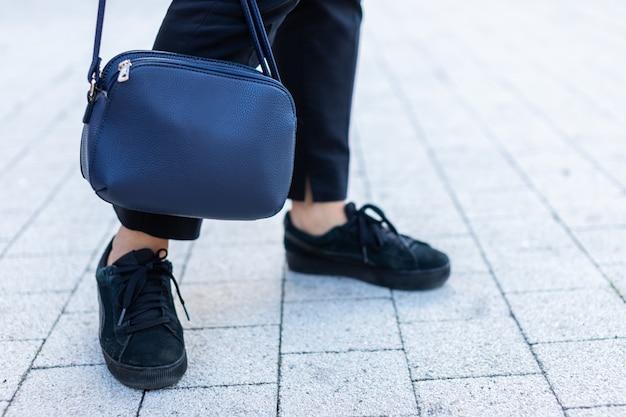 Primo piano della borsa e gambe di donna in scarpe da ginnastica sul marciapiede.