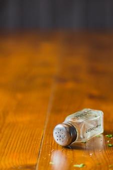 Primo piano della bottiglia dell'agitatore sulla tavola di legno