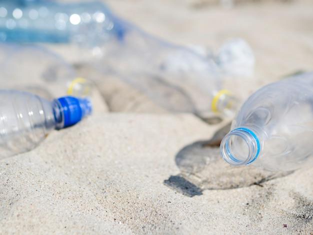 Primo piano della bottiglia di acqua di plastica residua vuota sulla sabbia