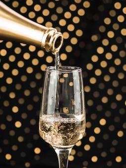 Primo piano della bottiglia di champagne che versa in vetro