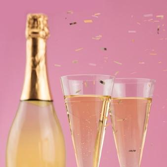 Primo piano della bottiglia di champagne con bicchieri e coriandoli