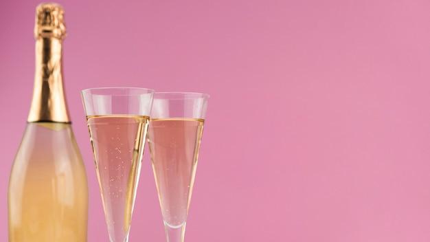 Primo piano della bottiglia di champagne con i vetri e lo spazio della copia