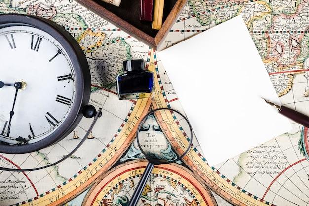 Primo piano della bottiglia di inchiostro, orologio e lente di ingrandimento sulla mappa