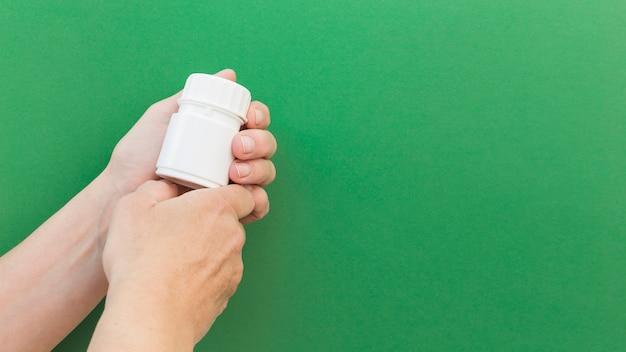 Primo piano della bottiglia di plastica della pillola della holding della mano contro priorità bassa verde