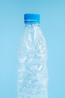 Primo piano della bottiglia di plastica su fondo blu