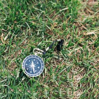 Primo piano della bussola di navigazione su erba verde