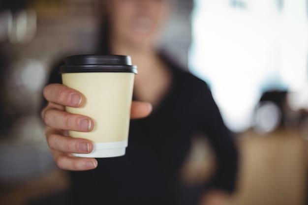 Primo piano della cameriera di bar che sta con la tazza di caffè eliminabile