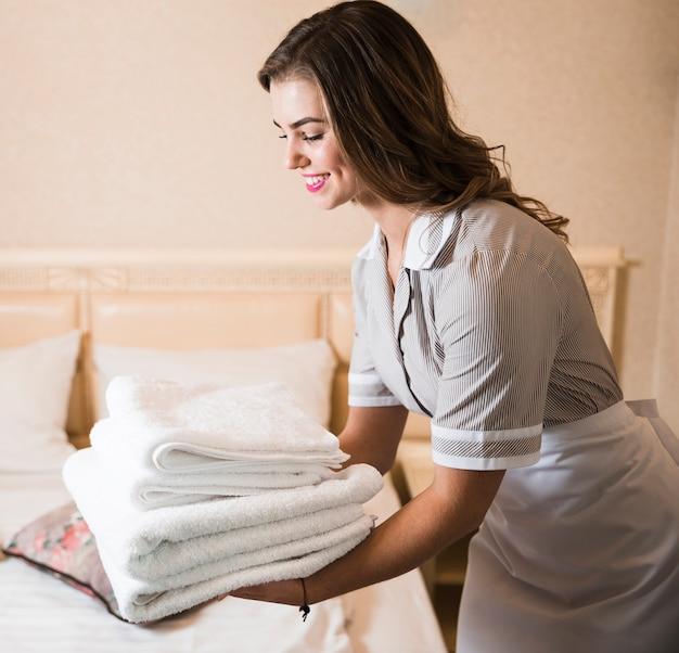 Primo piano della cameriera felice che mette pila di asciugamani di bagno bianchi freschi sul letto