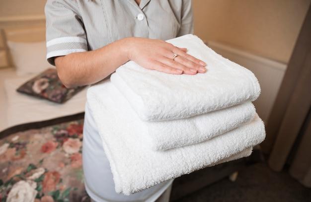 Primo piano della cameriera femminile che tiene asciugamano piegato molle pulito a disposizione