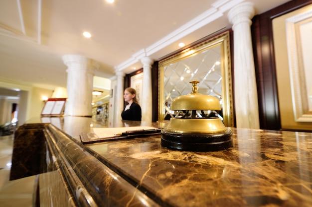 Primo piano della campana dell'hotel su una priorità bassa degli interiori e delle ragazze lussuosi
