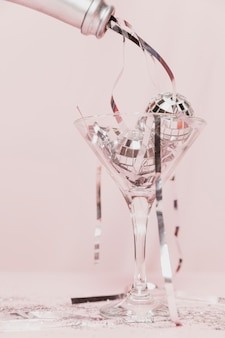 Primo piano della canutiglia di versamento della bottiglia di champagne in vetro