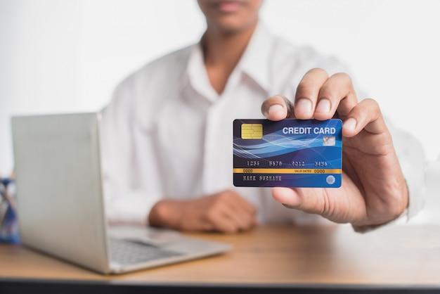 Primo piano della carta di credito blu tenuta a mano. focus sulla carta. concetti di shopping online.