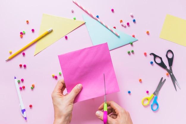 Primo piano della carta di taglio a mano di una persona sopra lo sfondo rosa