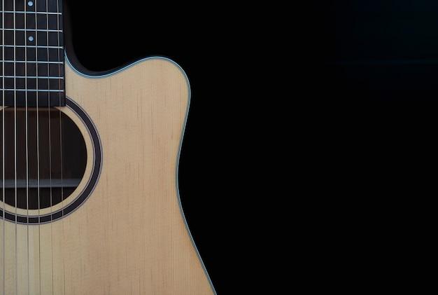 Primo piano della chitarra acustica tagliata sopra fondo nero