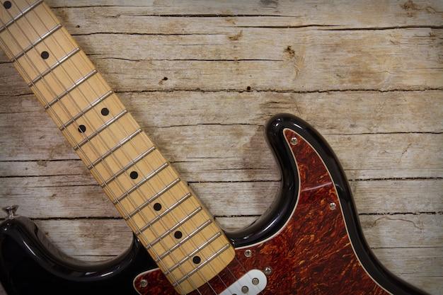 Primo piano della chitarra elettrica che si trova sul fondo di legno d'annata, con lo spazio della copia