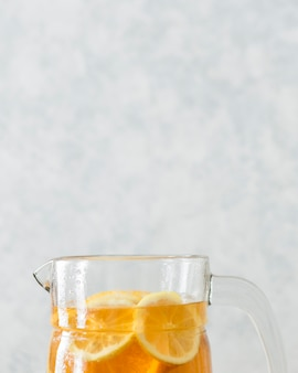 Primo piano della cima di vetro con le fette del limone