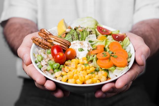 Primo piano della ciotola della tenuta dell'uomo di alimento sano