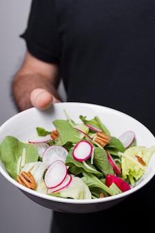 Primo piano della ciotola della tenuta dell'uomo di insalata