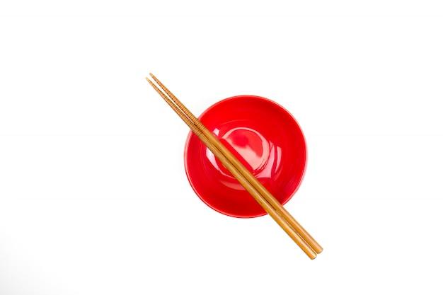 Primo piano della ciotola rossa con le bacchette di legno giapponesi