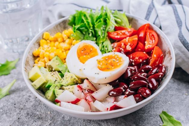 Primo piano della ciotola sana del pranzo del vegano. insalata di verdure con avocado, uovo, ravanello, mais, foglie verdi