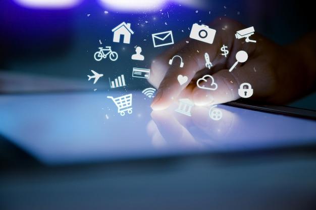 Primo piano della compressa digitale commovente del dito con l'icona dell'applicazione